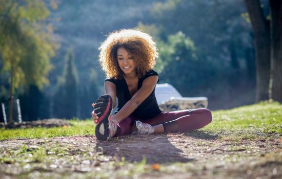 young fitness black woman runner stretching legs after run